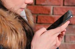 Closeupkvinna` s räcker att bläddra internetsidor på mobiltelefonsammanträde parkerar in royaltyfri bild