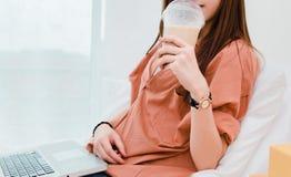 Closeupkvinna som dricker kallt kaffe och använder bärbara datorn royaltyfri foto