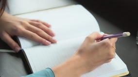 Closeupkvinnahand som hemma skriver på anteckningsboken på tabellen, flickaarbete med boken eller dagboken arkivfilmer