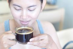 Closeupkvinnahand som rymmer exponeringsglas av varmt americanokaffe för drink med lycklig framsidakänsla, selektiv fokus, tappni arkivbild