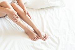 Closeupkvinnan lägger benen på ryggen på vitt säng, skönhet och begrepp för hudomsorg, s Arkivbilder