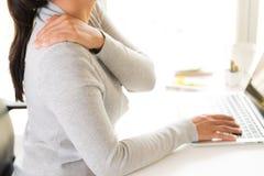 Closeupkvinnan med händer som rymmer hennes skuldra, smärtar arkivfoto