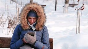 Closeupkvinnan sitter på bänk, och bläddra mobiltelefonen i vinter parkera i staden under dagen i snöig väder stock video