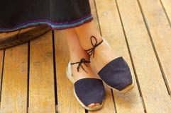 Closeupkvinnans fot som bär enkla traditionella andean skor, snör åt med fnuren som binds runt om lägre ben, korsade ben Arkivbilder