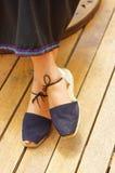 Closeupkvinnans fot som bär enkla traditionella andean skor, snör åt med fnuren som binds runt om lägre ben, korsade ben Arkivfoton
