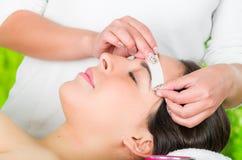 Closeupkvinnas framsida som mottar vaxbehandling för ansikts- hår, skönhet och modebegrepp Royaltyfri Foto
