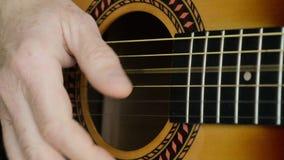 Closeuplängd i fot räknat av en man som spelar en akustisk gitarr stock video