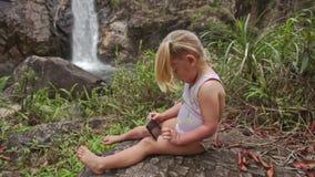 Closeuplilla flickan gör Selfie med telefonen på vattenfallet arkivfilmer