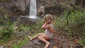 Closeuplilla flickan talar över telefonen på vattenfallet lager videofilmer
