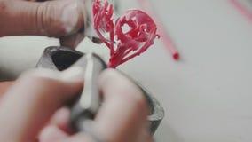 Closeupmakrofors Juveleraren klibbar försiktigt vaxmellanrum med pincett och en lödkolv för att skapa smycken arkivfilmer