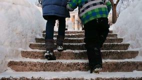 Closeupmamma- och sons ben som stiger upp på en snöig stege, trappuppgång Vinterstaden parkerar i snöig dag med fallande snö arkivfilmer