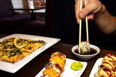 Closeupman som äter den läckra sushi med pinnar med mat i bakgrunden royaltyfri fotografi