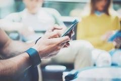 Closeupman som använder den moderna Smartphone handen Ungt samlat affärsfolk för grupp diskutera tillsammans det idérika idékafét royaltyfria foton