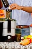 Closeupman& x27; s räcker genom att använda fruktsafttillverkaren som sätter in äpplestycken in i maskinen, det sunda livsstilbeg Arkivfoton