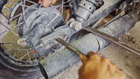 Closeupmanhänder monterar hjulet till motorcykeln Reparation-shoppar in arkivfilmer