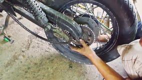 Closeupmanmonteringar rullar till motorcykeln Reparation-shoppar in stock video
