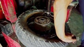 Closeupmannen installerar gummihjulet på jämviktsmaskinen shoppar in arkivfilmer