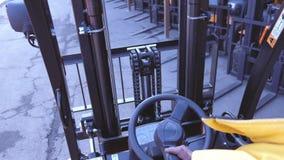 Closeupmannen kör en pålitlig gaffeltruckladdare för tung lastbil lager videofilmer