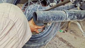 Closeupmannen monterar hjulet till motorcykeln Reparation-shoppar in arkivfilmer