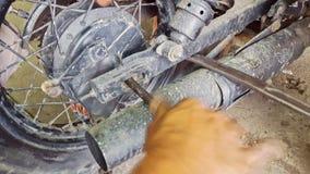 Closeupmanpassformer som axeln i motorcykel rullar Reparation-shoppar in lager videofilmer