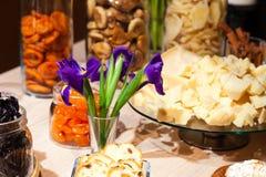 Closeupmellanmål, torkade frukter och muttrar i exponeringsglasbunke, blommairiers i vasen, platta med stycken med parmesanost Be arkivfoto