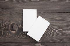 Closeupmodell av två vita buntar för affärskort på brun träbakgrund Mall för att brännmärka identitet arkivfoto