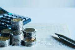 Closeupmynt, räknemaskin och bankbok på skrivbordet i regeringsställning för acco arkivfoto