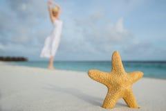 白色礼服跳舞的妇女在反对海星closeupops特写镜头的热带海滩 库存照片