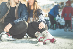 Closeuppar, flickor och pojkeskridskoåkning som är utomhus- på isbanan Arkivfoto