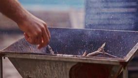 Closeuppersonvågor stiger ombord för att bränna torra pinnar i metallgaller arkivfilmer