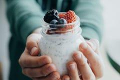 Closeuppojkehänder med pudding med frö, yoghurt och nytt för chia fotografering för bildbyråer