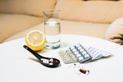 Closeuppreventivpillerar, citron och exponeringsglas av vatten på tabellen Royaltyfria Foton