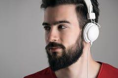 Closeupprofilsikt av den unga stiliga mannen med hörlurar som bort ser arkivfoto