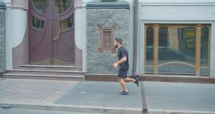 Closeupprofilstående av den vuxna caucasian sportiga manliga löparen som utomhus joggar ner gatan i den stads- staden stock video