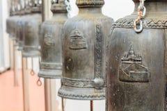 Closeuprad av klockor i buddistisk tempel i Thailand Royaltyfri Foto