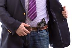 Closeups?kerhetsmedel i aff?rsdr?kt med handvapnet som f?stas p? b?ltet Isolerat p? vit royaltyfri fotografi