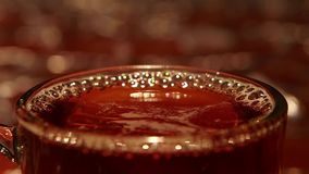 Closeups, bubbles on surface of hot freshly brewed black tea. Drink is poured into clean small transparent glass cup, small gold lights, mag reflects lights stock video footage