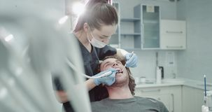 Closeups in a modern clinic room dentis make a oral hygiene procedure to the young man patient , in the dental room. 4k stock video footage