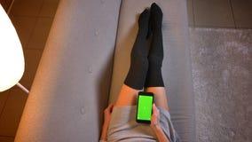 Closeups skjuter av den sociala massmediabloggeren för ungt attraktivt kvinnligt mode som använder telefonen med den gröna skärme arkivbild