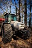 Closeupsidosikt av traktoren på stora hjul på vägen i skog Fotografering för Bildbyråer