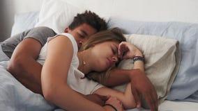 Closeupsikt av blandras- par som ligger i säng och sover, medan omfamna sig Ungt familjbegrepp arkivfilmer