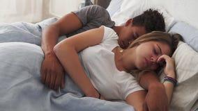 Closeupsikt av blandras- par som ligger i säng och sover, medan omfamna sig Ungt familjbegrepp stock video