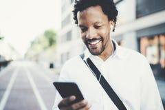 Closeupsikt av den attraktiva amerikanska afrikanska svarta mannen som lyssnar till musik med hörlurar i stads- bakgrund lyckliga Royaltyfria Foton