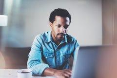 Closeupsikt av den eftertänksamma skäggiga afrikanska mannen som använder bärbara datorn på coworking utrymme på trätabellen Begr royaltyfri bild