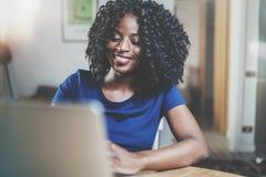 Closeupsikt av den funktionsdugliga bärbara datorn för lycklig afrikansk amerikankvinna, medan sitta på trätabellen i vardagsrumm royaltyfri fotografi