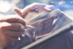 Closeupsikt av den hållande minnestavlan för affärsman förestående och genom att använda den elektroniska pennan, medan arbeta på Arkivfoton