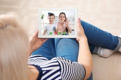 Closeupsikt av den h?ga kvinnan som talar med barnbarn via video pratstund arkivbilder