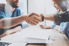 Closeupsikt av den manliga partnerskaphandskakningen för affär För coworkershandshaking för foto två process Lyckat avtal efter u arkivbild