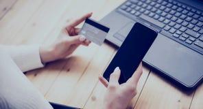 Closeupsikt av den unga kvinnan som gör online-shopping vid bärbara datorn och smartphonen Flicka som hem trycker på knappen på m royaltyfri bild