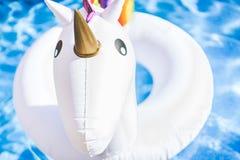 Closeupsikt av den uppblåsbara färgrika vita enhörningen på simbassängen Rolig tid i sommaren på simbassängen Begrepp arkivbild